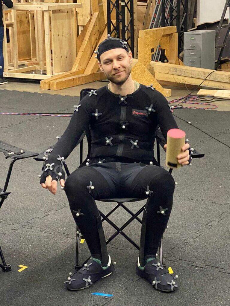 Dimitri Weideli sitting in a black mocap suit.