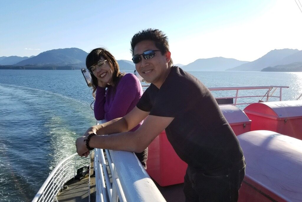 Elise Baldwin and Dennis Cheng smiling on a ferry boat with mountains behind them.